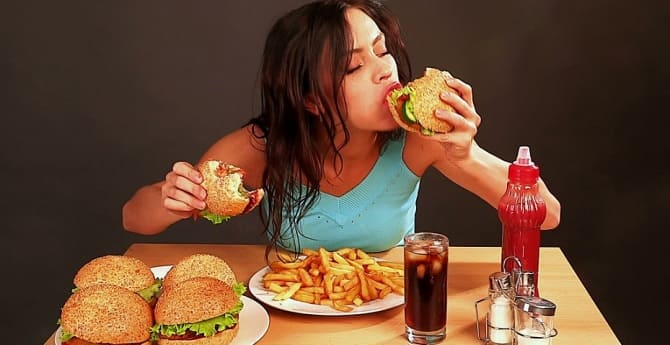 Девушка ест вредную пищу