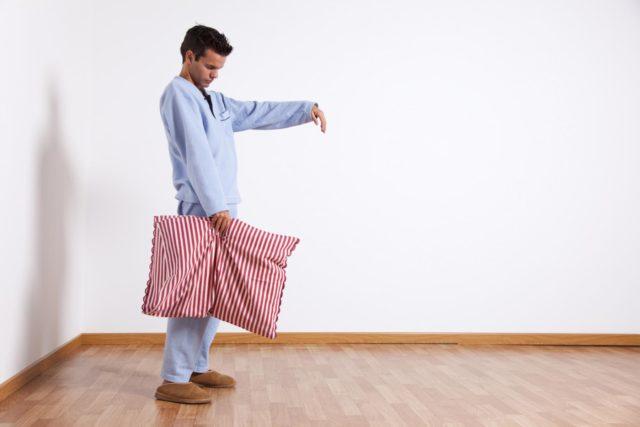 Мужчина держит подушку