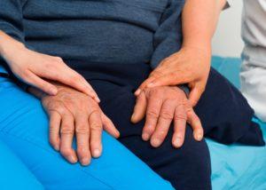 Женщины держат за руки старика