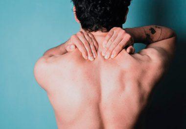 мужчина массирует свою шею