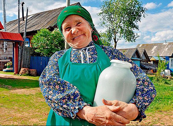 Бабушка держит банку с молоком